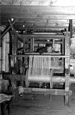 Een foto van één van de oude originele en nog handbediende weefgetouwen welke in gebruik is geweest bij 'De Driekleur'. Achter het weefgetouw : Jacob Veldhuizen.