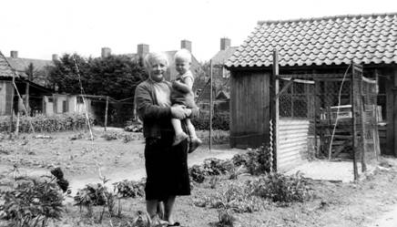 Oma Wagensveld in haar  moestuin aan de Lindenlaan 22. Op de achtergrond de huizen van de Acacialaan.